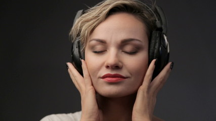 Woman blonde closeup listening to music. Relaxation, emotions.