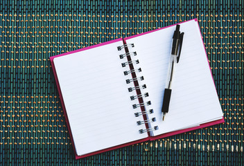 notepad and pen on mat