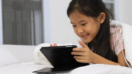Little Asian girls using tablet on the bed, pan camera