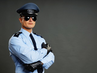 Portrait of policeman in sunglasses gray background