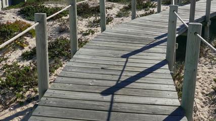 Walking on Wooden Footpath through Dunes Atlantic Ocean Beach