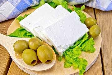 Feta with olives and lettuce on board and spoon