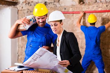 Architektin und Bauarbeiter auf Baustelle mit Bauplan