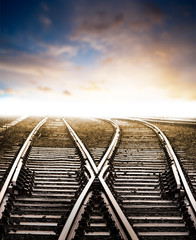 Rain wet railway tracks, dramatic sunset sky