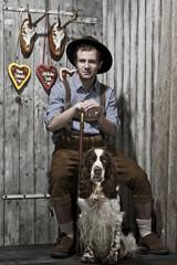junger Mann in Lederhose mit einem Hund