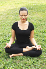 Woman in meditation pose on the green grass