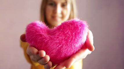 Teen girl offering a fluffy heart