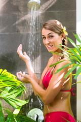 Woman in tropical garden having shower outdoors