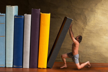 man supporting falling book in the bookshelf