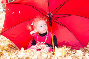 Fall. Cute child girl playing with fallen leaves in autumn