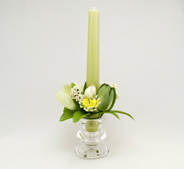 Candle holder with green pillar candle against white background