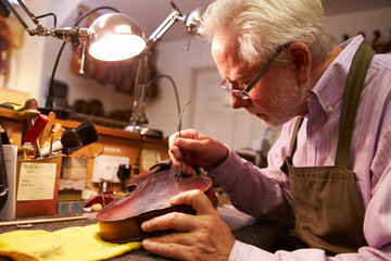 Man Restoring Violin In Workshop