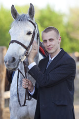 groom with grey horse