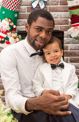 Happy black father and baby boy cuddling by fireplace.