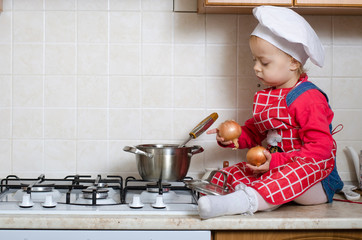 Little chef puts into the pot vegetables