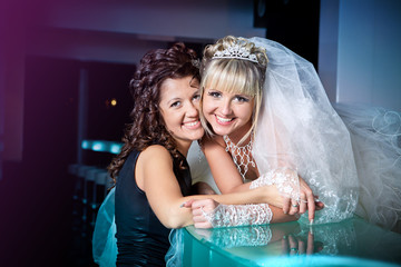 happy bride and her sister in wedding day stand near bar