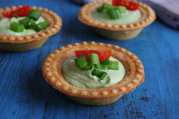 Tartlets with greens and vegetables with sauce on table