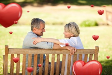 Composite image of happy retired couple sitting on the bench