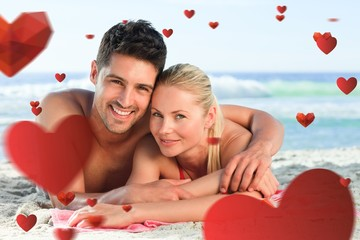 Composite image of lovers lying down on the beach
