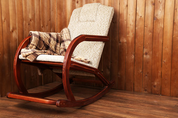 Rocking chair covered with plaid on wooden wall background