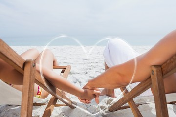 Composite image of couple resting on deck chairs