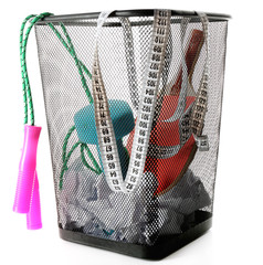 Metal trash bin with sport equipment, crumpled paper and weight