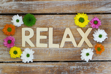 Relax written with wooden letters, santini flowers
