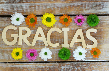 Gracias written with wooden letters on wood, santini flowers