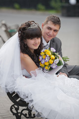 groom and the bride sit on a bench