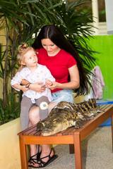Mom and child girl on Crocodile farm in Phuket, Thailand