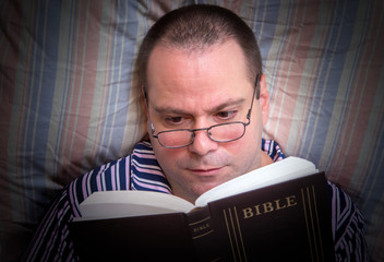 man reading the Bible in bed