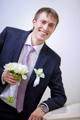 Portrait of the groom with a bouquet of roses