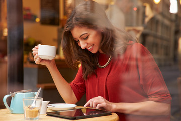 Woman Viewed Through Window Of Cafe' Using Digital Tablet