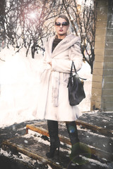 woman standing on the porch in the winter in a white fur coat