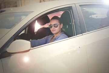 young girl in sunglasses driving a car rides