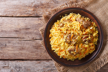 Asian pilaf on a brown plate. horizontal top view, rustic