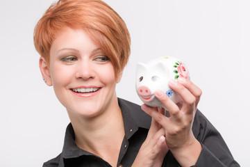 Junge Frau freut sich mit Sparschwein