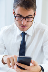 Young handsome man working in his office with mobile phone.