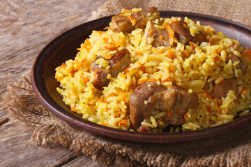 pilaf with meat and vegetables close up on a plate. horizontal