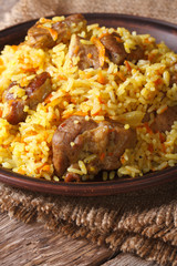 pilaf with meat and vegetables close up on a plate. Vertical