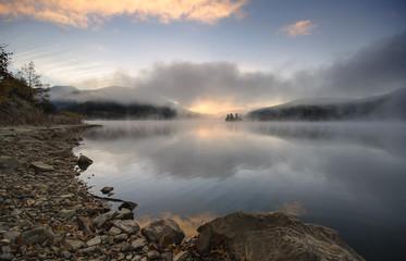 Sunrise in lake with morning fog