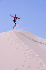 Young on top of a dune,jumping on the sand