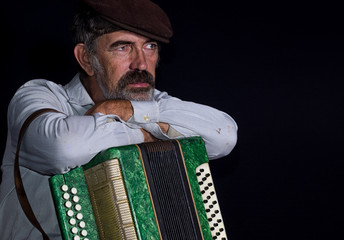 Portrait of an old country man with button accordion