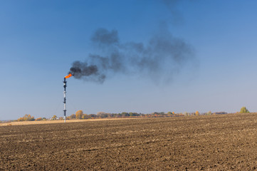 Ukrainian landscape with pipe of burning oil-well gas