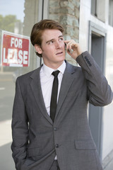 man in front of a store on the phone