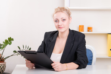 Pretty young female employee at the desk in the office