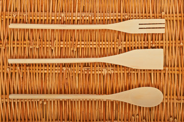 A set of wooden spoons on  natural basket textures background.