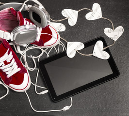 Love for music concept.Red sneakers, headphones, tablet,hearts.