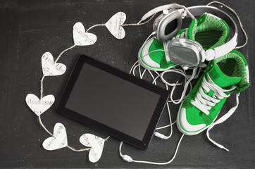 Love for music concept. Green sneakers, headphones, tablet and h