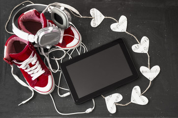 Love for music concept. Red sneakers, headphones, tablet and hea